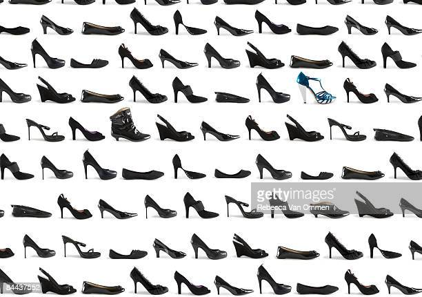 uma grade de muitos calçados preto e um sapato azul - sapato preto - fotografias e filmes do acervo