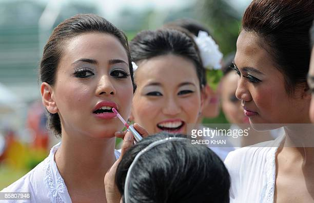A gridgirls gets last touches to her makeup before the start of the Malaysian Grand Prix in Sepang on April 5 2009 Jenson Button pushed his Brawn GP...