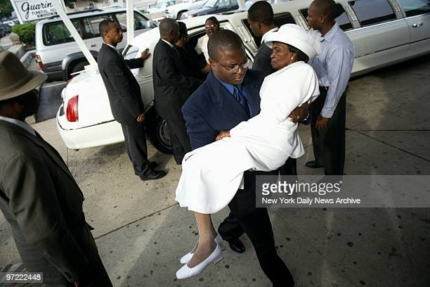 A griefstricken Vierge Auguste mother of Wendy's massacre victim Jean Dumel Auguste is carried into the wake for her son at the Guarino Funeral Home...