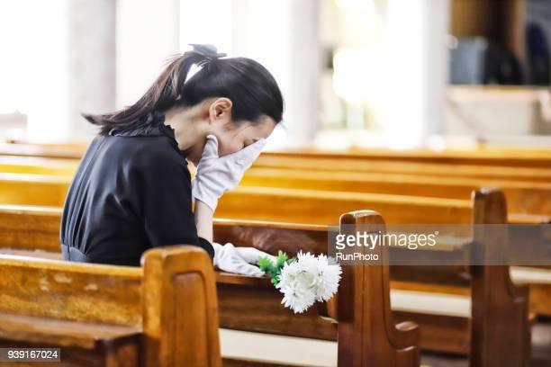 grieving bereaved at church - begrafenis stockfoto's en -beelden