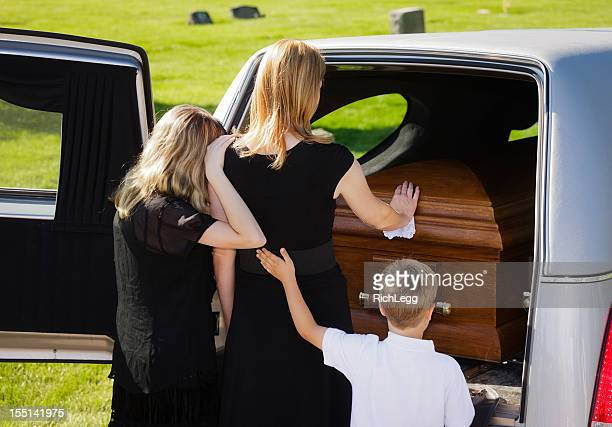 grieving family at a funeral - hearse stock photos and pictures