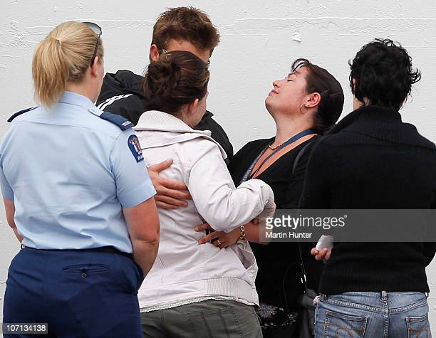 Grieving family members embrace before a visit by Prime Minister John Key to meet with families of the lost miners on November 25 2010 in Greymouth...