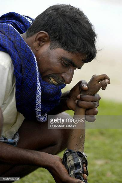 A grieving Indian father cries over the dead body of his child at Silver Beach in Cuddaloresome 185 kms south of Madras 27 December 2004 after tidal...