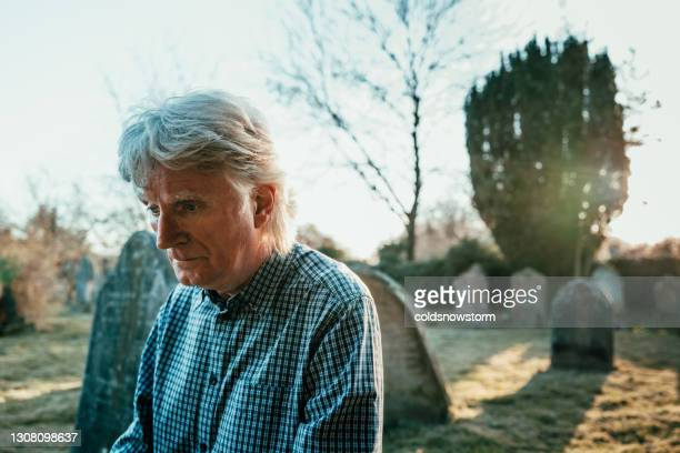 grieving man praying in cemetery - memorial event stock pictures, royalty-free photos & images
