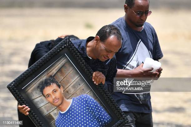 A grieving relative carries the picture of a victim at the crash site of the Ethiopian Airlines operated Boeing 737 MAX aircraft at Hama Quntushele...