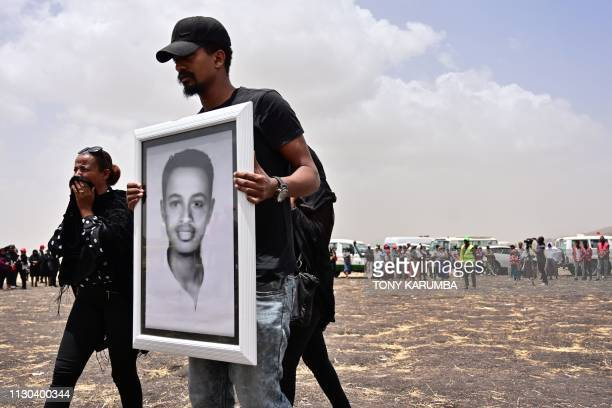 A grieving relative carries the portrait of a victim as he arrives at the crash site of the Ethiopian Airlines operated Boeing 737 MAX aircraft at...