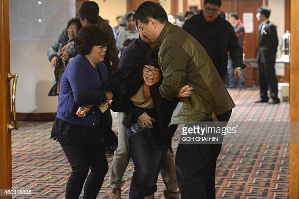 Grieving relatives of passengers on Malaysia Airlines flight MH370 leave a hotel hall at after being told the news that the plane plunged into Indian...