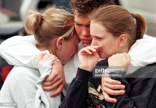 Grieving students support each other in the parking lot of Clemmet Park near Columbine High School 21 April 1999 in Littleton CO Residents and...