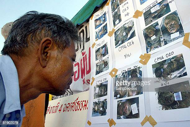 A grieving Thai man tries to identify his relatives from pictures of dead bodies pasted outside a makeshift relief camp in the Khao Lak 30 December...
