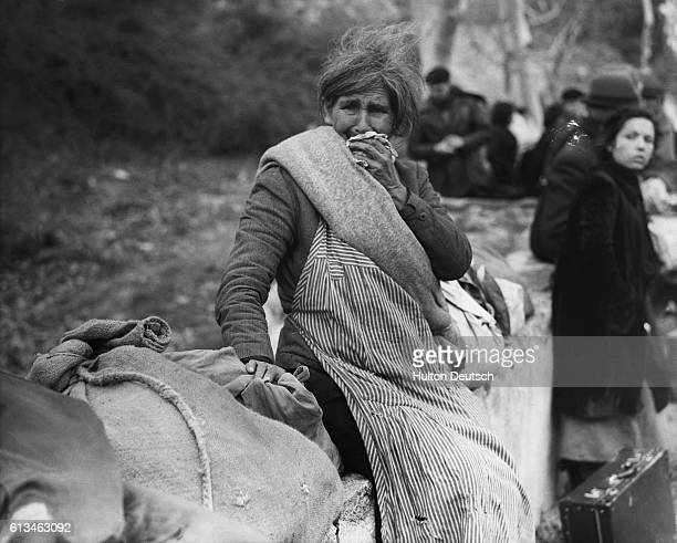 A grieving woman sits among the few possessions she could carry from Spain into France where she has fled seeking refuge from the Spanish Civil War...