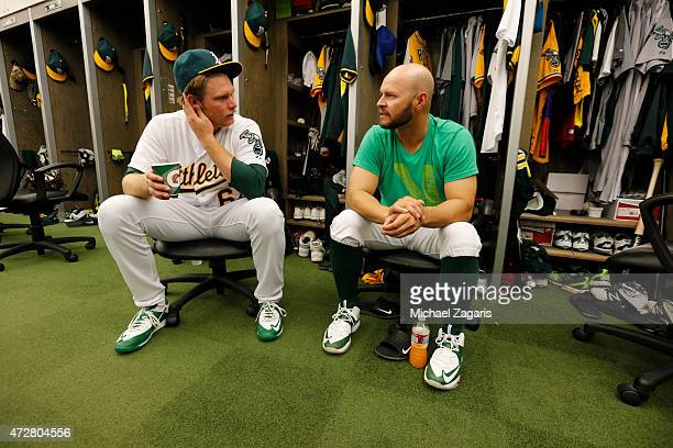 J Griffin and Cody Ross of the Oakland Athletics talk in the clubhouse prior to the game against the Los Angeles Angels of Anaheim at Oco Coliseum on...