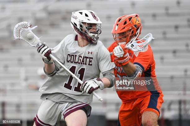 Griffin Brown of the Colgate Raiders dodges to the goal against the defense of Duke Repko of the Bucknell Bison during the second half at Andy Kerr...