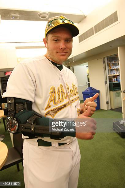 Griffin of the Oakland Athletics stands in the clubhouse with his arm braced up after Tommy John surgery prior to the game against the Detroit Tigers...