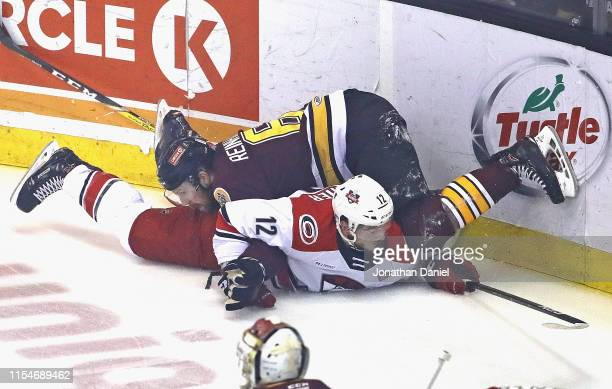 Griffin Reinhart of the Chicago Wloves lands on top of Julien Gauthier of the Charlotte Checkers during game Five of the Calder Cup Finals at...
