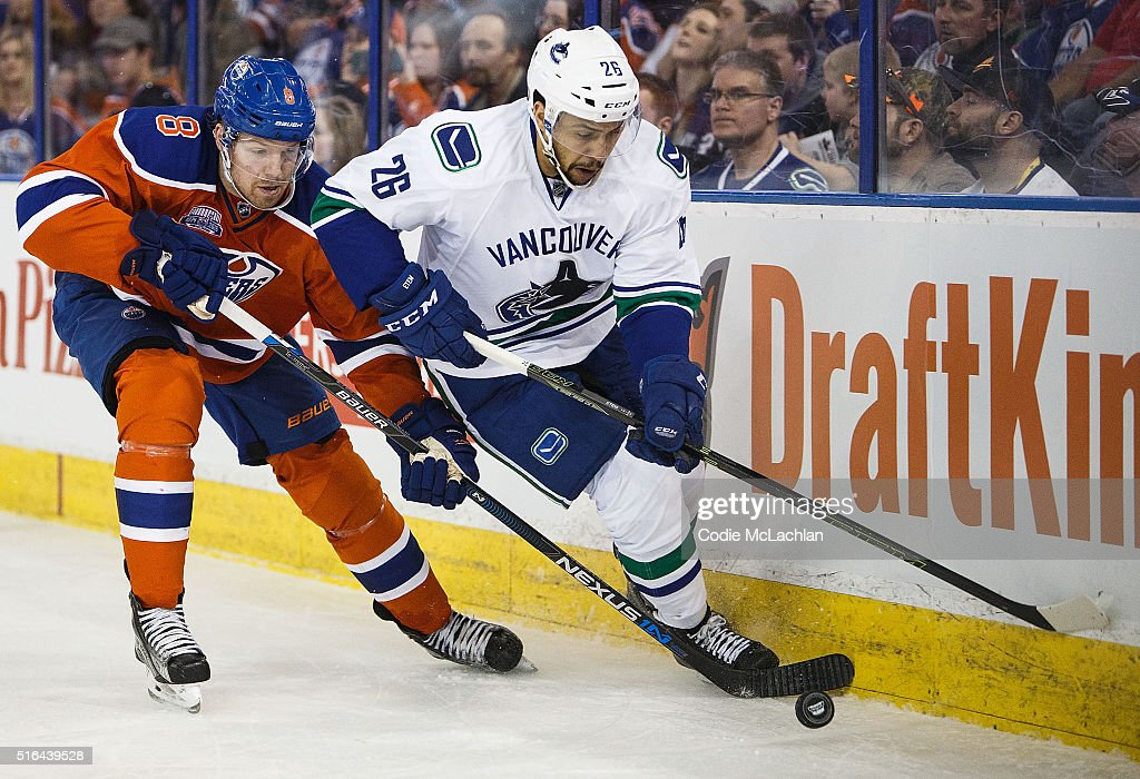 Griffin Reinhart #8 of the Edmonton Oilers defends against Emerson Etem #26 of the Vancouver Canucks on March 18, 2016 at Rexall Place in Edmonton, Alberta, Canada.