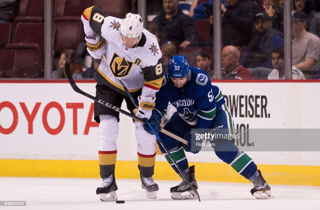 Griffin Reinhart #8 of the Vegas Golden Knights and Cole Cassels #52 of the Vancouver Canucks get tangled up while battling for the puck in NHL pre-season action on September 17, 2017 at Rogers Arena in Vancouver, British Columbia, Canada.