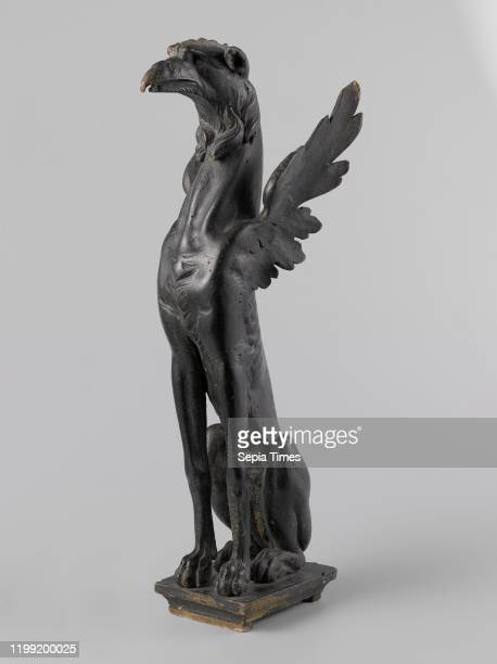 Griffin with accompanying velvet pedestal On a rectangular skirting board is the griffin formed from an elongated dog body with wings on the...
