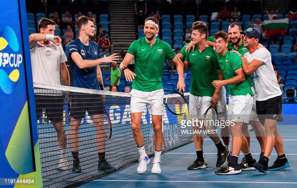 Grigor Dimitrov and Alexandar Lazarov of Bulgaria celebrate with teammates after winning their men's doubles match against Jamie Murray and Joe...