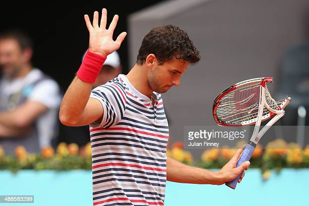 Grigor Dimitrov of Bulgaria apologizes after he smashed his racket in his match against Marius Copil of Romania during day five of the Mutua Madrid...