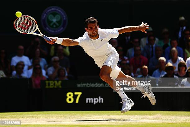 Grigor Dimitrov of Bulgaria dives to make a return during his Gentlemen's Singles semifinal match against Novak Djokovic of Serbia on day eleven of...