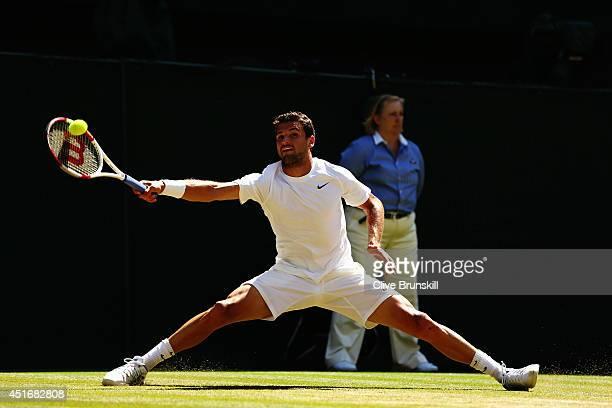 Grigor Dimitrov of Bulgaria does the splits as he makes a return during his Gentlemen's Singles semifinal match against Novak Djokovic of Serbia on...