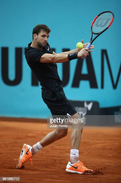 Grigor Dimitrov of Bulgaria in action against Dominic Thiem of Austria during day six of the Mutua Madrid Open tennis at La Caja Magica on May 11...