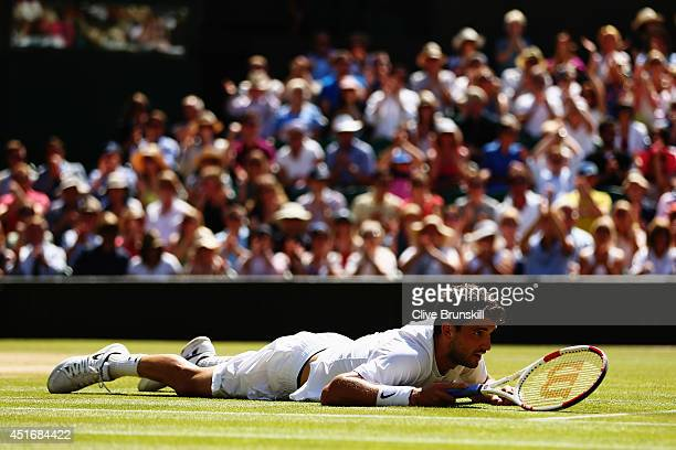 Grigor Dimitrov of Bulgaria lies flat out after slipping over during his Gentlemen's Singles semifinal match against Novak Djokovic of Serbia on day...