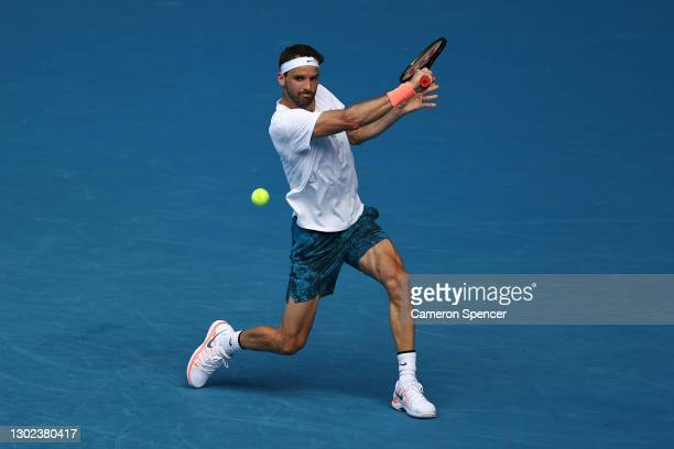 Grigor Dimitrov of Bulgaria plays a backhand in his Men's Singles Quarterfinals match against Aslan Karatsev of Russia during day nine of the 2021...