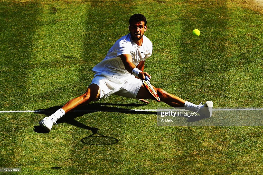 Grigor Dimitrov of Bulgaria plays a shot whilst sitting down after slipping over during the Gentlemen's Singles semi-final match against Novak Djokovic of Serbia on day eleven of the Wimbledon Lawn Tennis Championships at the All England Lawn Tennis and Croquet Club on July 4, 2014 in London, England.