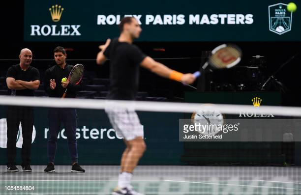 Grigor Dimitrov of Bulgaria plays a volley while coach Andre Agassi and Danny Valverdu look on during practice ahead of the Rolex Paris Masters on...