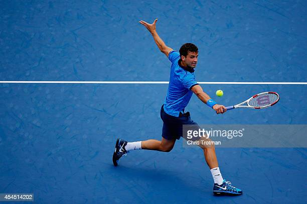 Grigor Dimitrov of Bulgaria returns a shot against Gael Monfils of France in their men's singles fourth round match on Day Nine of the 2014 US Open...