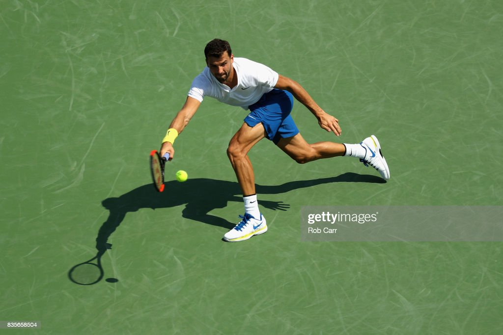 Grigor Dimitrov of Bulgaria returns a shot to John Isner during Day 8 of the Western and Southern Open at the Linder Family Tennis Center on August 19, 2017 in Mason, Ohio.