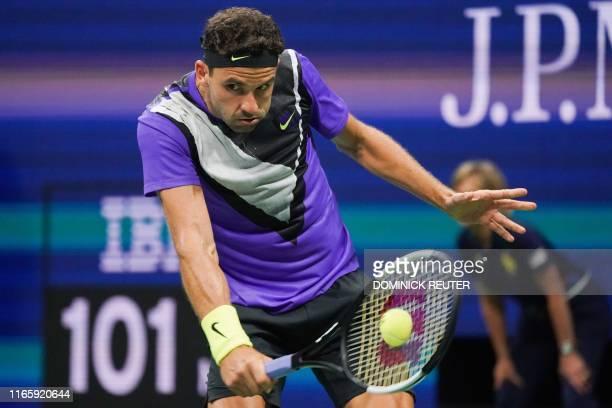 Grigor Dimitrov of Bulgaria returns the ball against Roger Federer of Switzerland in their Men's Singles Quarterfinals tennis match during the 2019...