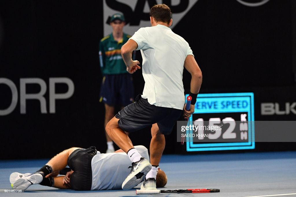 Grigor Dimitrov of Bulgaria (R) rushes to help Kyle Edmund of Britain, who fell due to a leg injury, during their men's singles quarter-final match at the Brisbane International tennis tournament at the Pat Rafter Arena in Brisbane on January 5, 2018. / AFP PHOTO / Saeed KHAN / IMAGE
