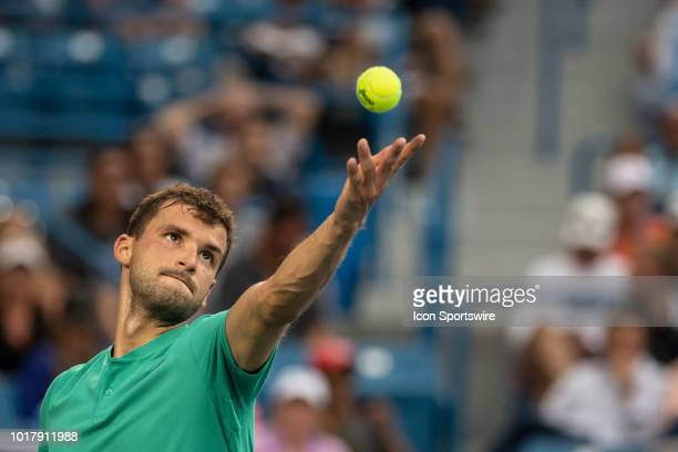 Grigor Dimitrov of Bulgaria serves to Novak Djokovic of Serbia during Day 5 of the Western and Southern Open at the Lindner Family Tennis Center on...