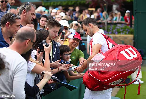 Grigor Dimitrov of Bulgaria signs autographs after winning the Men's Singles first round match against Bjorn Fratangelo of The United States on day...
