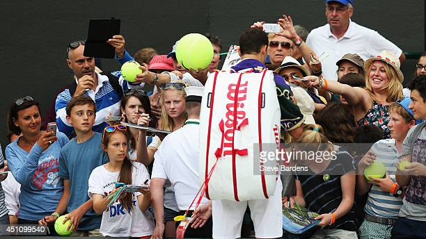 Grigor Dimitrov of Bulgaria signs autographs for fans following his win in the Gentlemen's Singles first round match against Ryan Harrison of the...