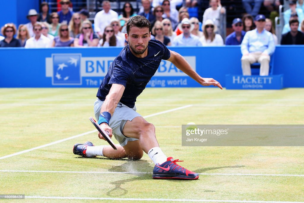 Grigor Dimitrov of Bulgaria slides for a ball in his match against Stan Wawrinka of Switzerland during their Men's Singles semi-final on day six of the Aegon Championships at Queens Club on June 14, 2014 in London, England.