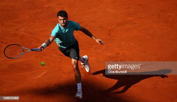 Grigor Dimitrov of Bulgaria stretches to play a forehand against Marcos Baghdatis of Cyprus in their first round match during day one of the...