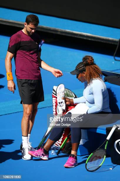 Grigor Dimitrov of Bulgaria takes a look at the new shoes of Serena Williams of the USA during a practice session together ahead of the 2019...
