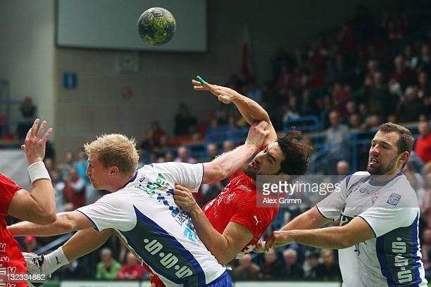Grigorios Sanikis of Melsungen is challenged by Sverre Jakobsson and Joakim Larsson of Grosswallstadt during the Toyota Handball Bundesliga match...