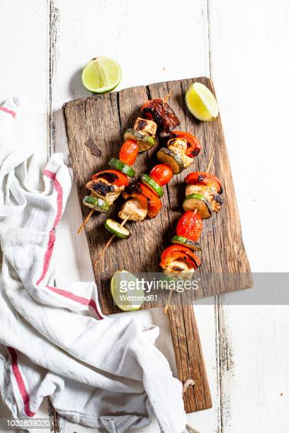 grill skewers with grilled chicken, tomato, bell pepper and zucchini on chopping board - bratspieß stock-fotos und bilder