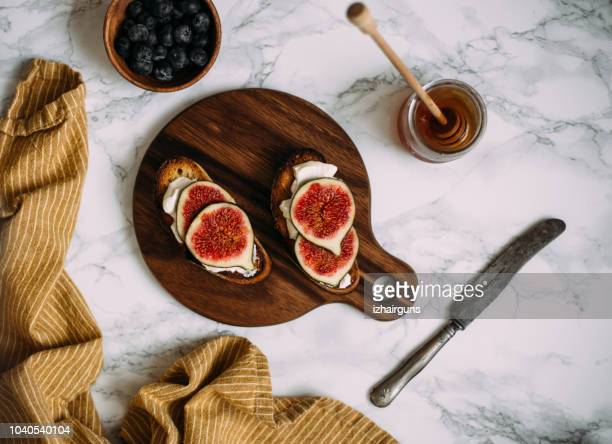 grill toast with honey, cream cheese or ricotta and fresh ripe figs on cutting board. - fig stock pictures, royalty-free photos & images