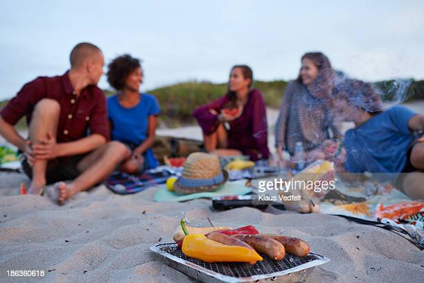 Grill with snack pepers & sausages, people unsharp