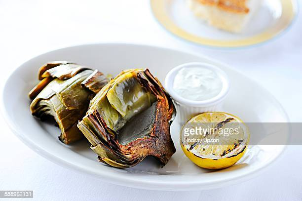 Grilled artichokes with lemon on restaurant table