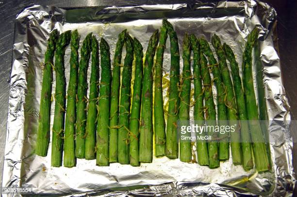 Grilled asparagus with grated lemon zest and olive oil on a baking tray covered with aluminium foil