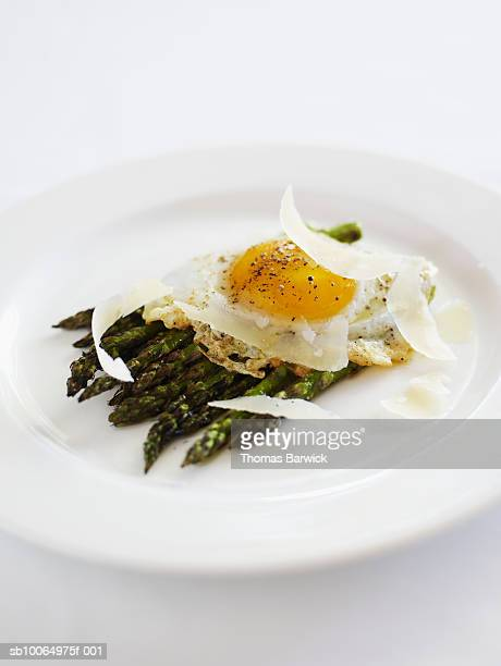 Grilled asparagus with parmesan and fried duck egg, close-up