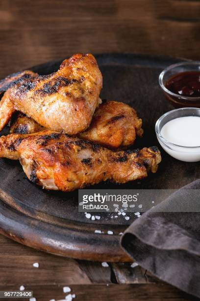 Grilled BBQ chicken meat wings and legs served on round wood chopping board with two sauces and salt on gray textile over dark wooden background