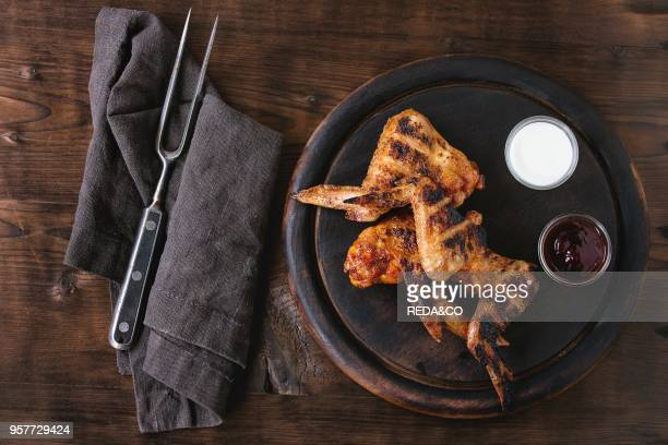 Grilled BBQ chicken meat wings served on round wood chopping board with two sauces salt and vintage meat fork on gray textile over dark wooden...