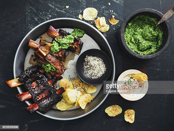 Grilled beef ribs with potato chips and parsley sauce